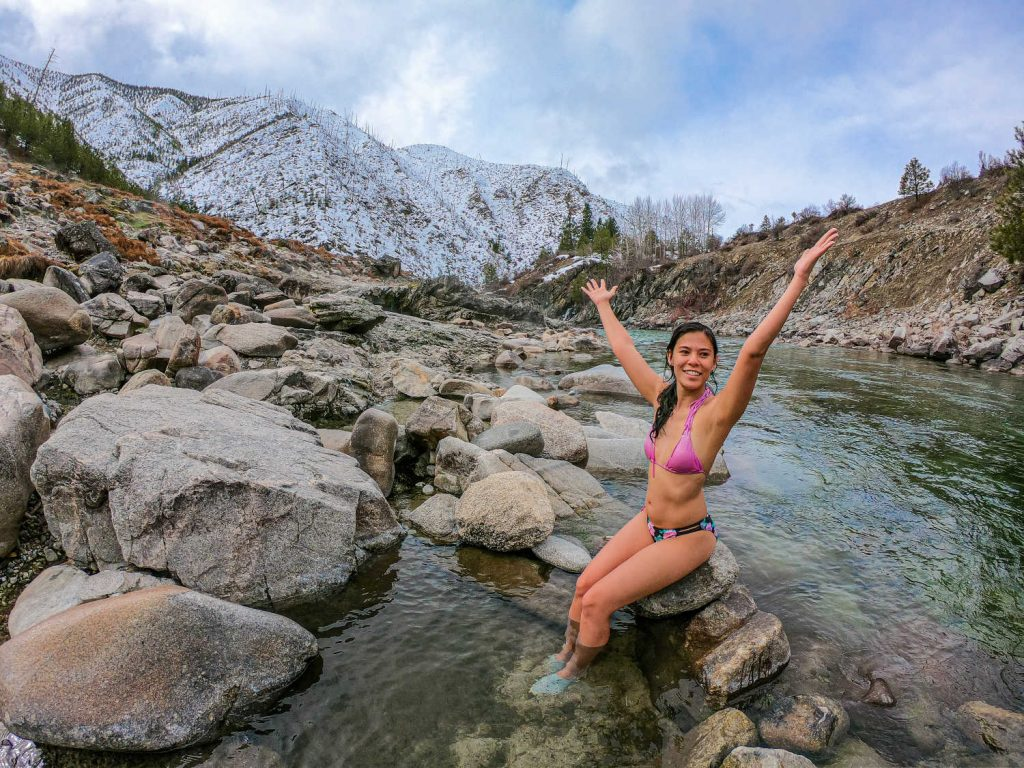Woman sitting in natural hot spring with arms up in the air.