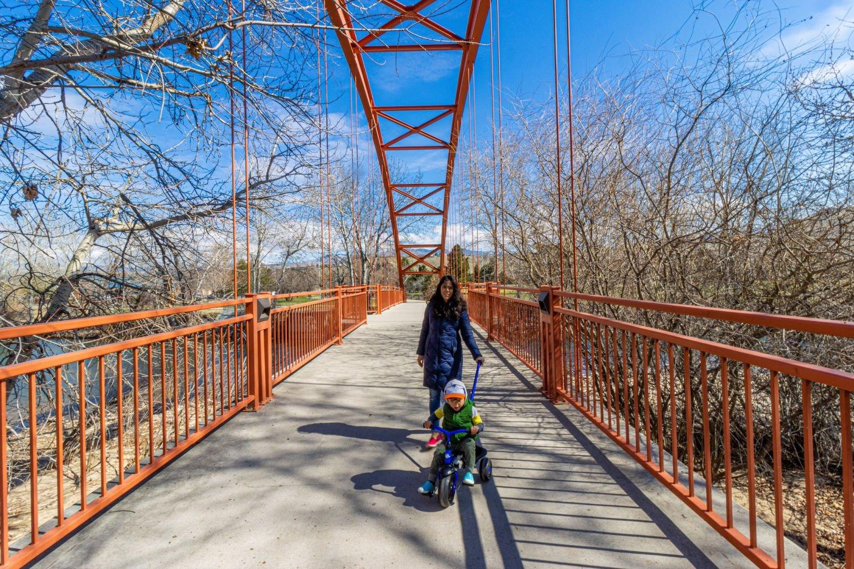 Mom and kid biking on a bridge in Boise Idaho
