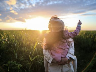 women traveling with daughter pointing at sun