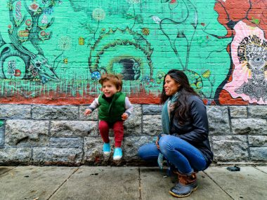 mother and child in front of mural in freak alley