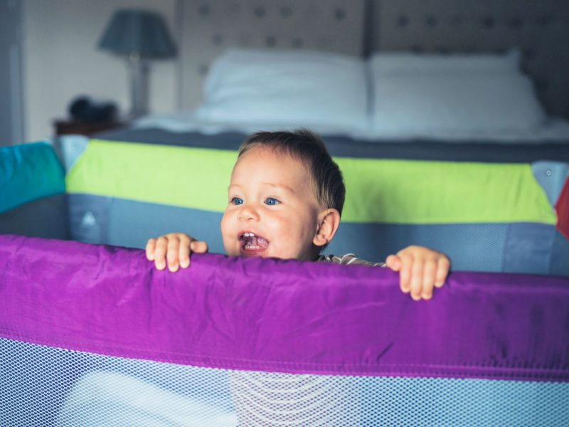 baby looking over travel crib