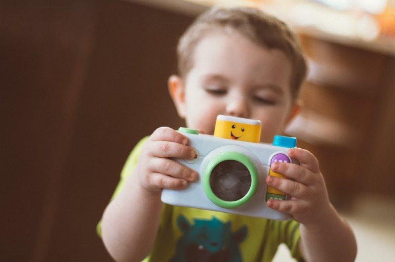 toddler holding camera toy