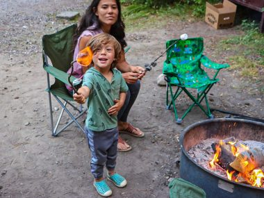 toddler beside a campfire holding up a marshamallow straight to camerawomen