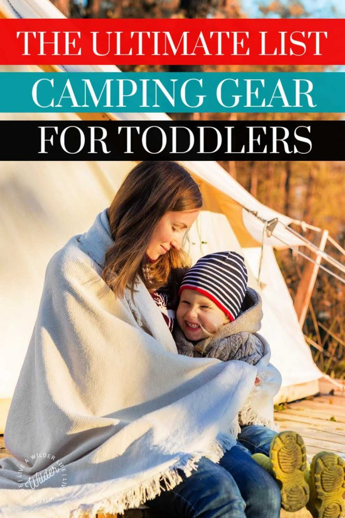 camping gear for toddlers Pinterest pin. Mom and toddler sit in front of canvas tent wrapped up in blanket together.