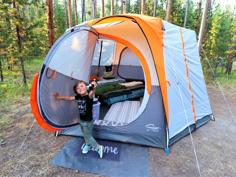 young boy toddler sticking out a toy in front of a large tent in a campsite