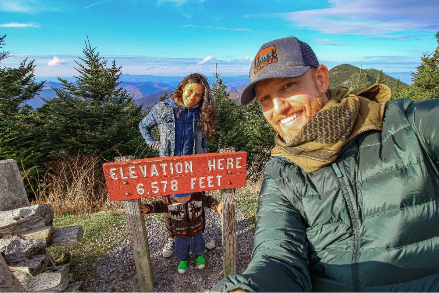 an adventurous family of three posing in front of a high elevation sign