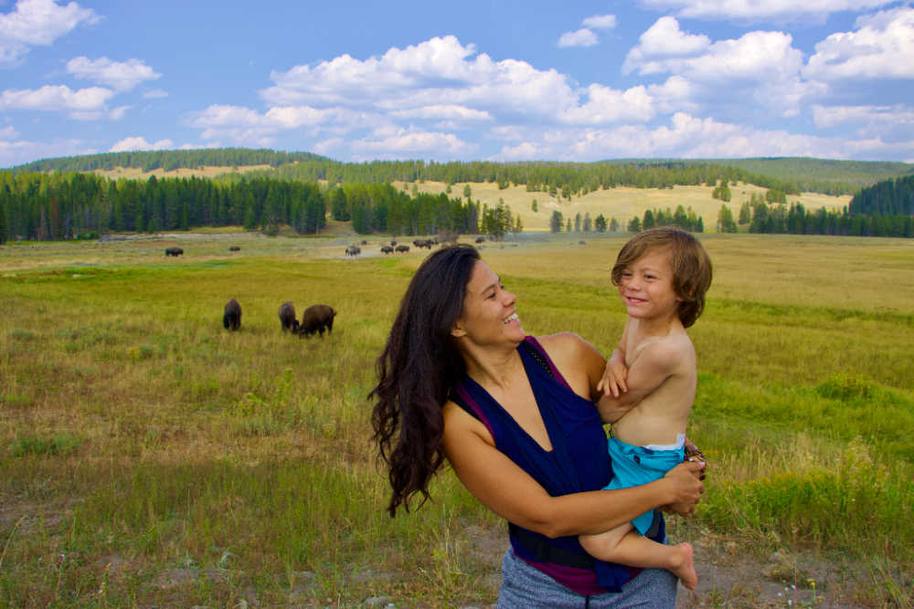 mom and son standing in front of bison at Yellowstone National Park