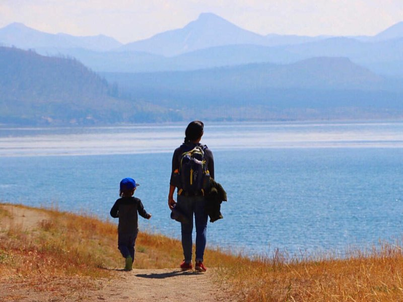 Woman walking on cliff overlooking water in yellowstone with kid