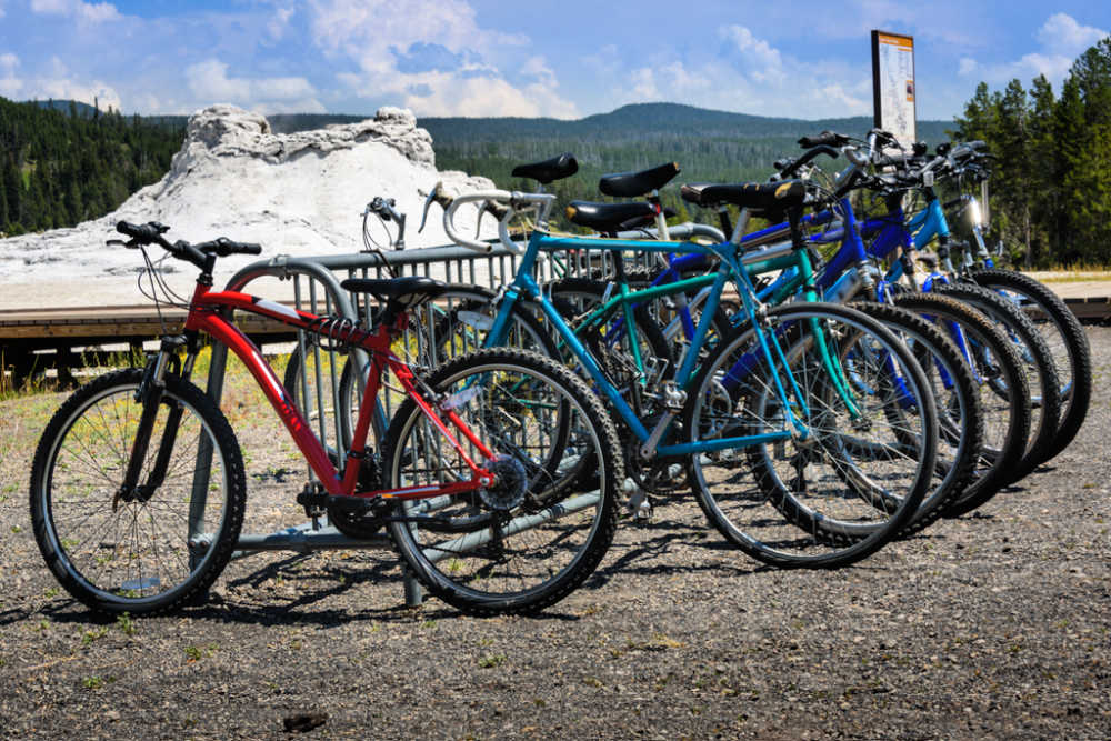 bicycles on a rack in front of Old Faithful