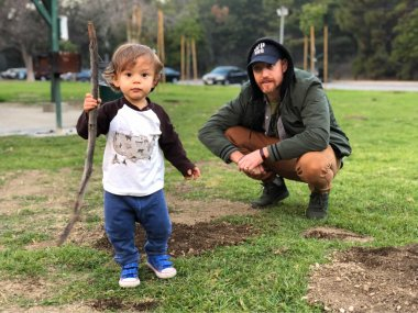 toddler boy holding up stick to camera as dad watches from behind