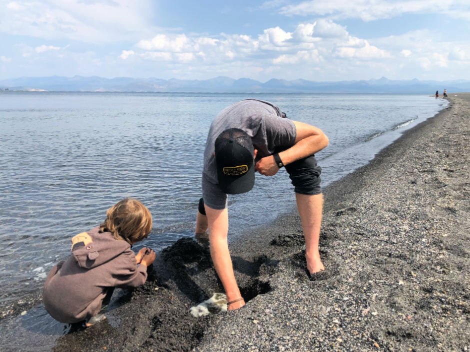 father and son playing with sand at Lake Yellowstone