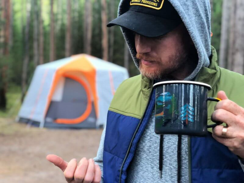 man holding camping coffee cup in front of tent in Yellowstone