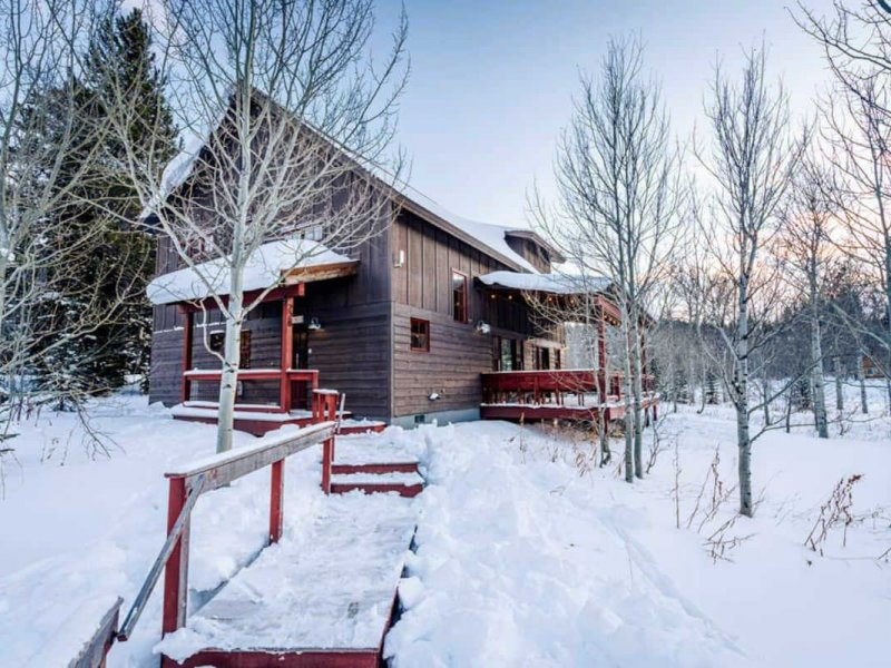 Snowy winter day in front of a Yellowstone Airbnb cabin