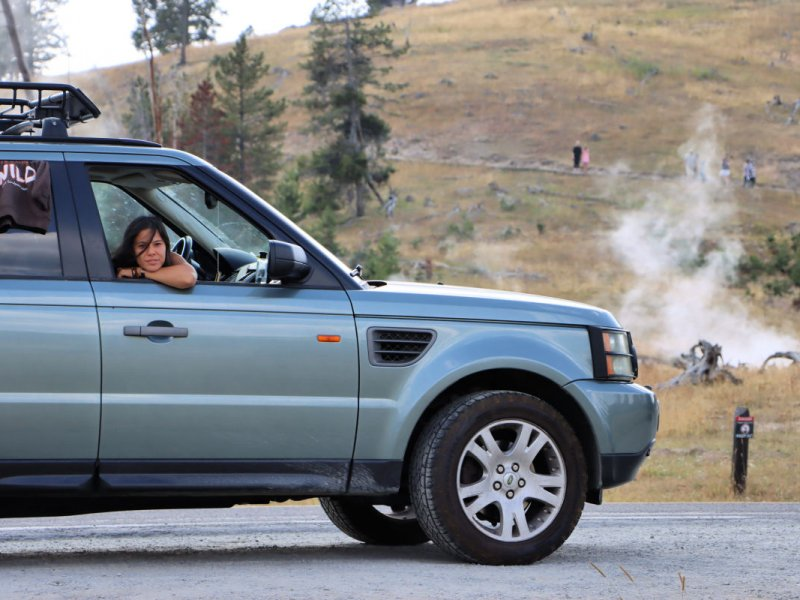 woman looking out of passenger side window of green SUV with steam rising up from a hot spring behind the car