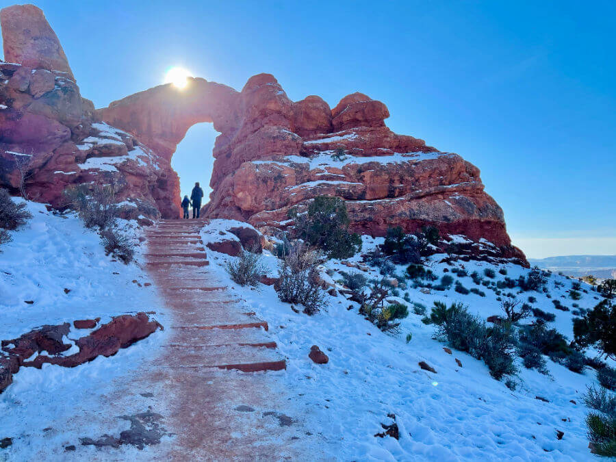 woman and young child standing under natural red arch in the desert with snow on ground.
