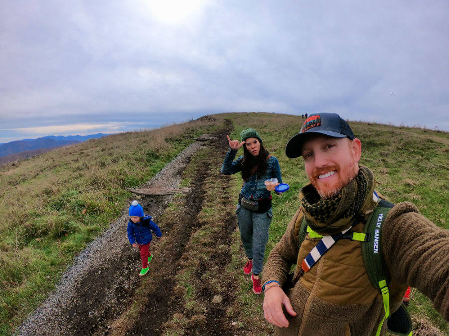 Hip, outdoor family takes a selfie while hiking with toddler along mountain ridge.