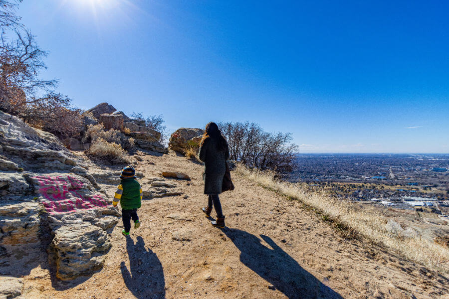 woman and toddler hiking in a high desert landscape with a city in the background