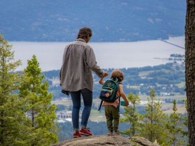 woman hiking with a toddler and holding his hand on a rocky outlook overlooking a lake.