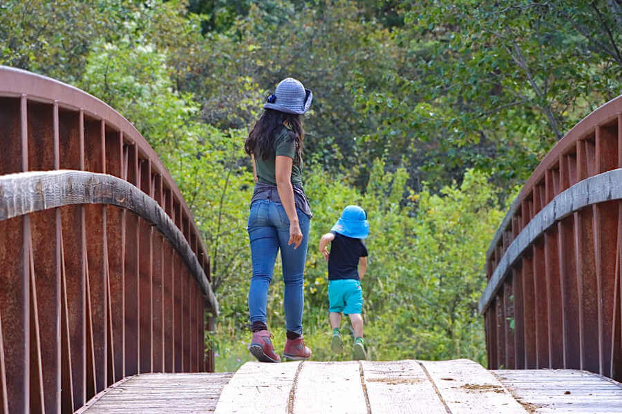 Back view of woman and toddler skipping over a bridge towards a forest.