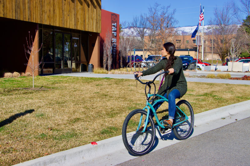 Woman on cruiser bicycle looking at a Boise Brewery