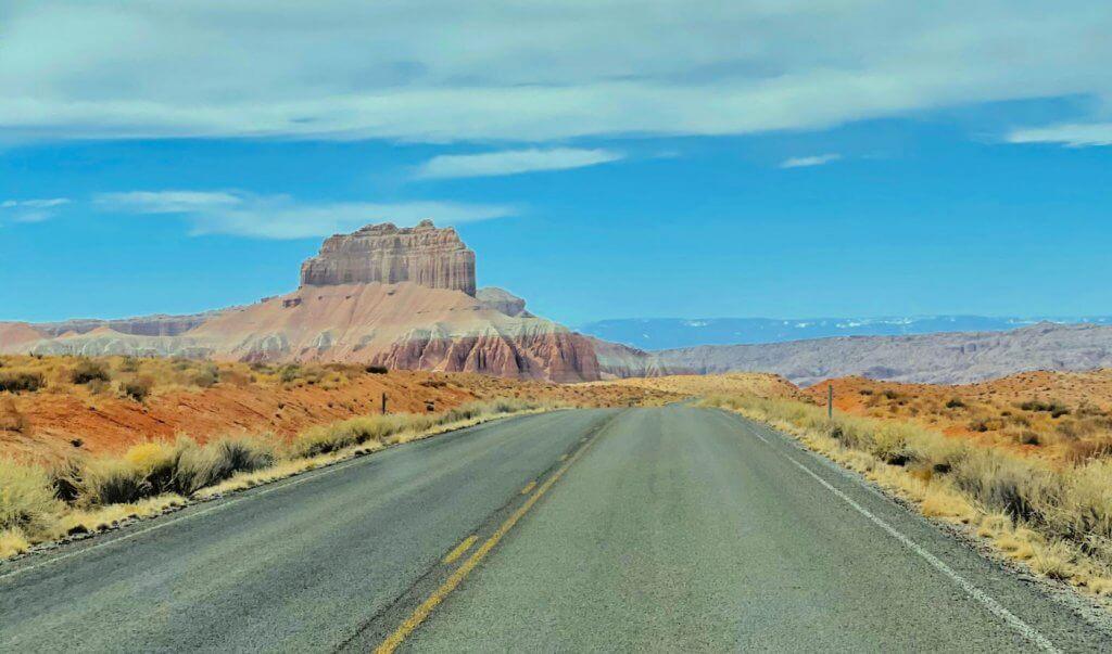 empty desert road leading to Utah National Parks