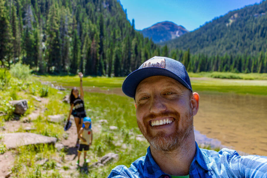 A family going on a bucket list adventure. A hip father taking selfie with mountains, wife, and toddler in background.