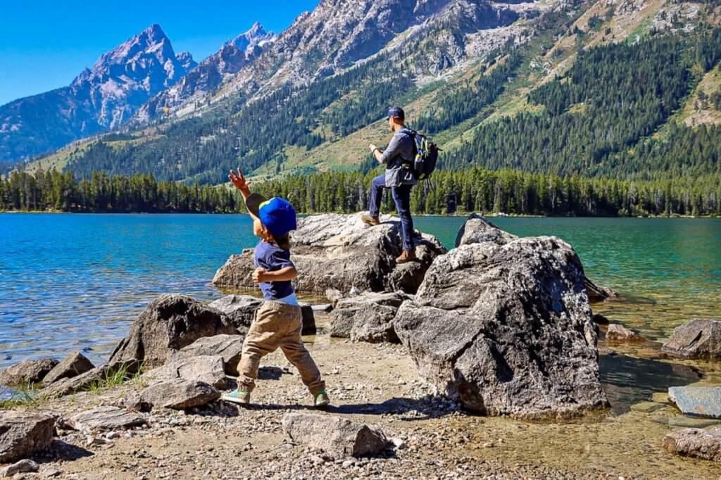 man and son on a bucket list adventure throwing rocks into blue waters near Teton mountain range.