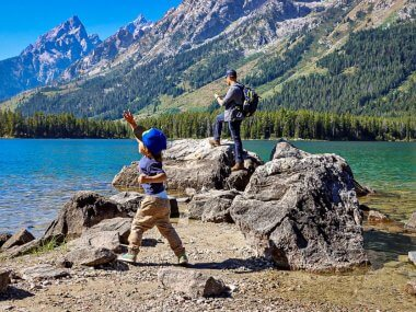 man and son on a bucket list adventure throwing rocks into blue waters near Teton mountain range.
