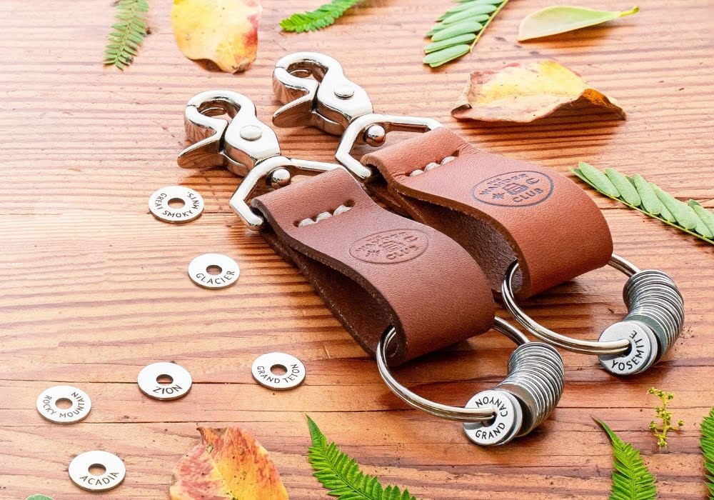 two brown leather keychains with national park tokens sitting on top of a wooden table