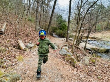 little boy running on a trail in the forest