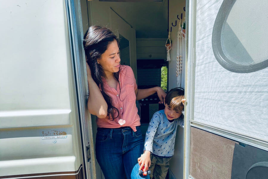 mom and toddler son standing at doorway of vintage camper