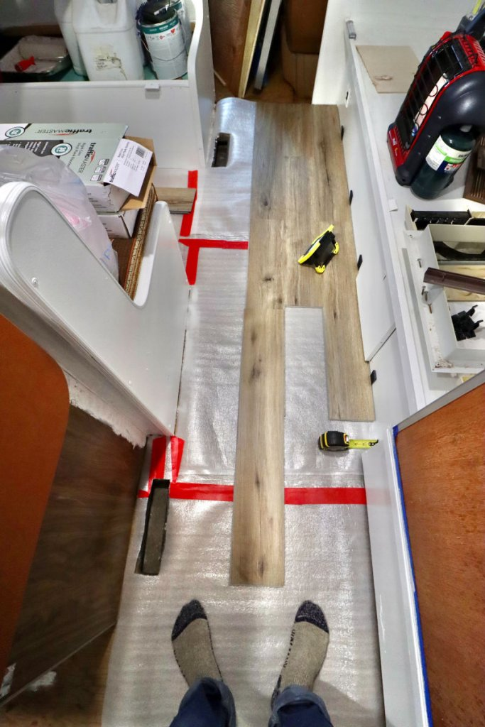 Feet standing on new wooden floors being put into old camper