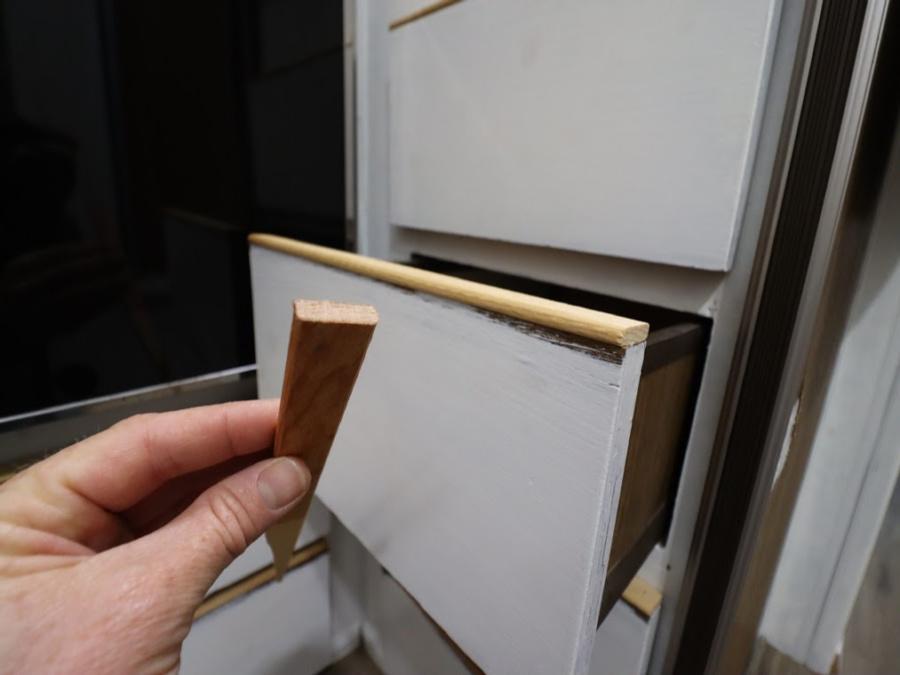 hand placing decorative trim on drawers