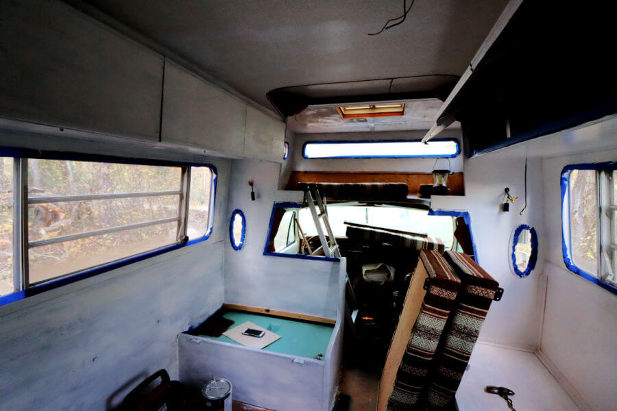 A renovated camper in the process of being painted white