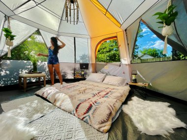 woman stands in a big tent set up for glamping