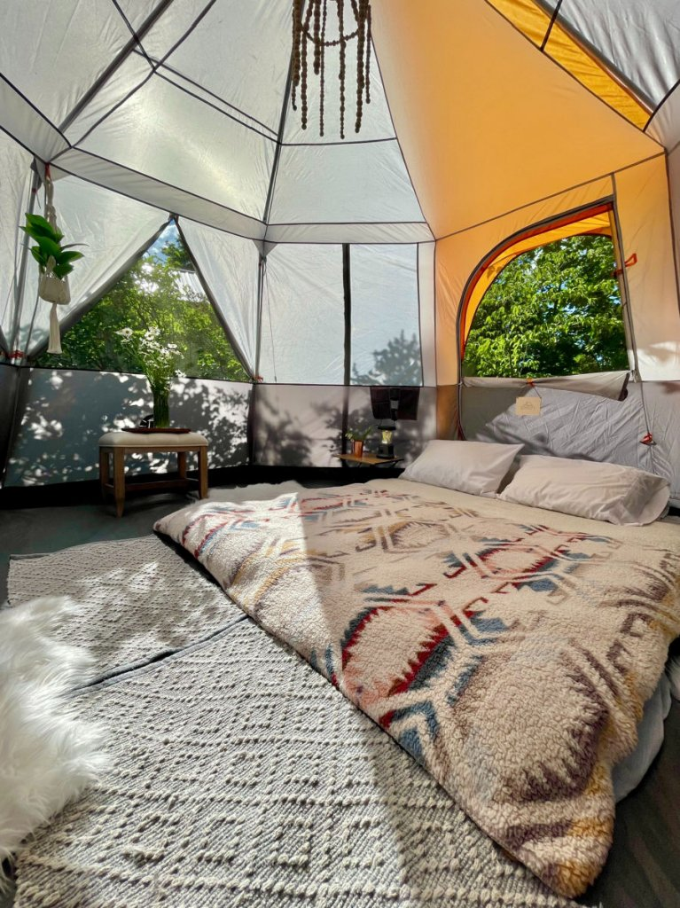 beautiful bohemian bed on ground of glamping tent
