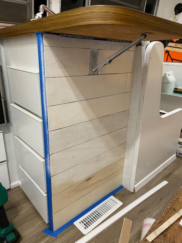 Whitewashed shiplap in kitchen peninsula of renovated camper
