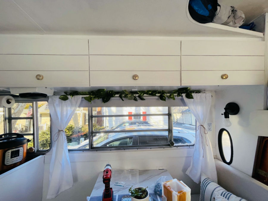 gold knobs on white cabinets of a newly renovated camper