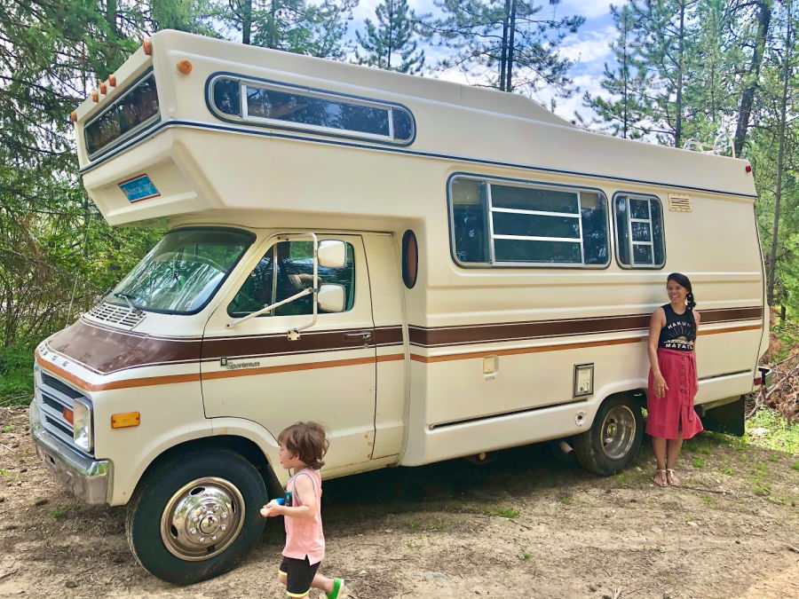 trendy mother and toddler stand in front of vintage 1979 camper