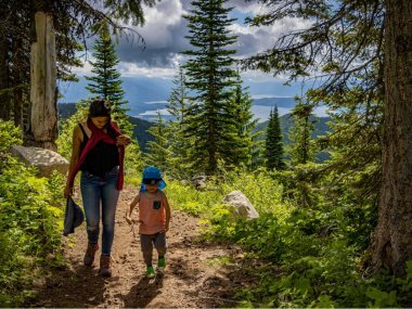 mother and son hiking in a lush pine forest