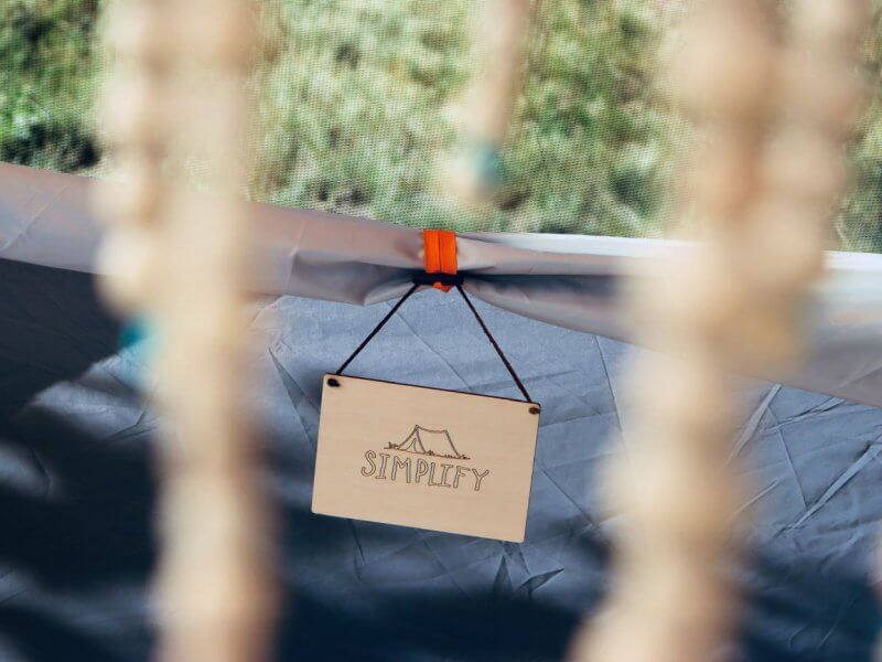 """a wooden sign with a tent hanging from a glamping tent that says """"simplify"""""""