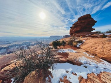 Sweeping view of canyonlands national park in winter with snow on red rocks and canyons in the distance.