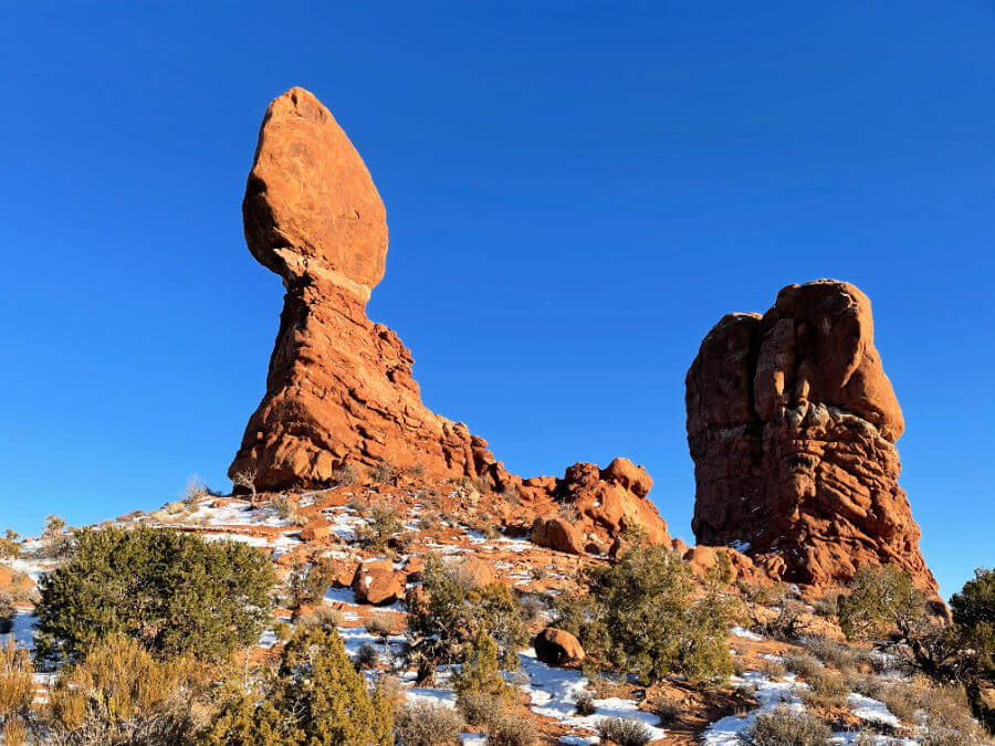 A massive red rock that appears to be balancing on a rock structure.