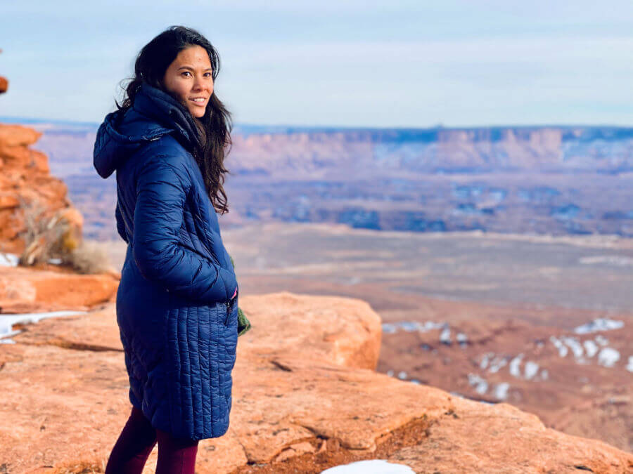 woman in long dark blue winter jacket standing at edge of cliff in Canyonlands national park