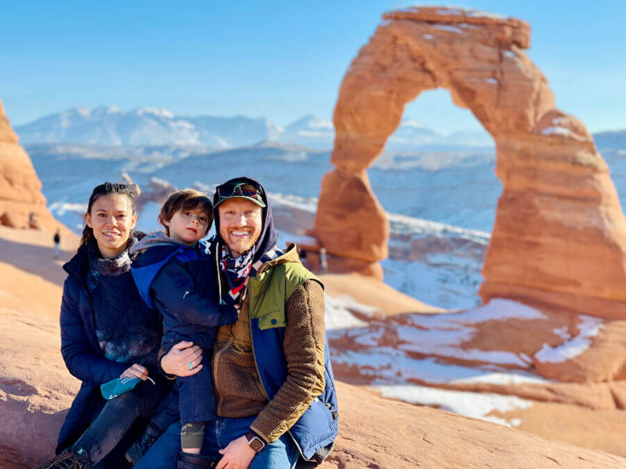 a family of three with a young boy sitting in front of delicate arch in arches national park