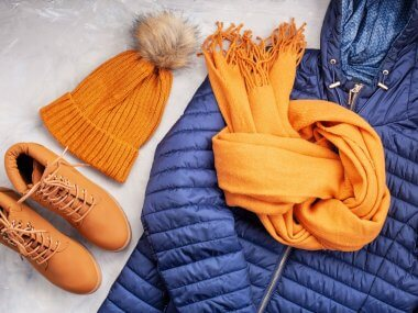 flat lay of winter clothing for a winter cabin packing list