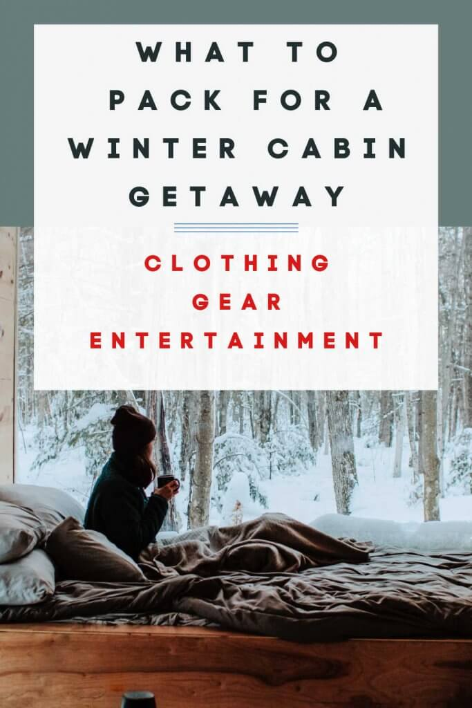 """Pinterest image of a woman in a bed  holding a cup of coffee looking out a large window in a winter cabin at a snowy forest. Words say """"what to pack for a winter cabin getaway."""""""