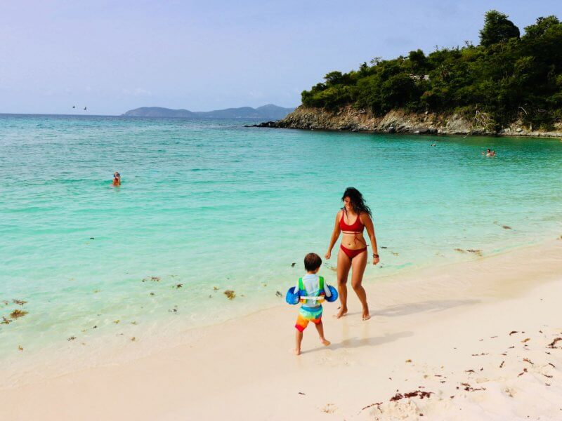 mom and son playing on bright carribbean beach of St John.