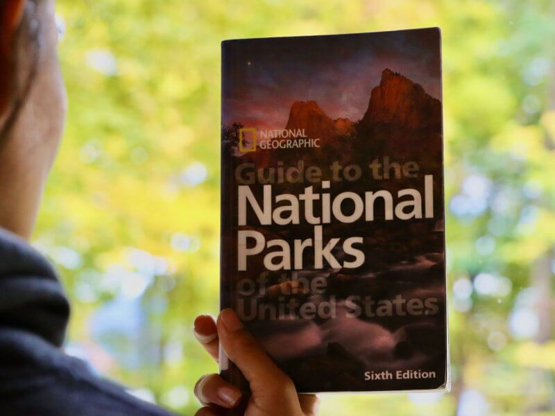 woman holding a national parks book with bright green trees in the distance